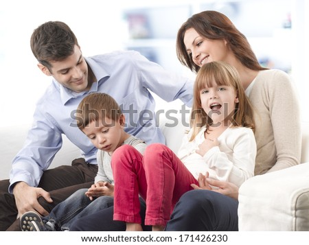 Happy young family sitting on sofa in living room