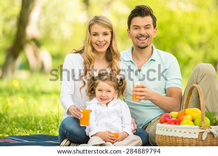 Happy young family sitting on the lawn in park and drinking juice. - stock photo