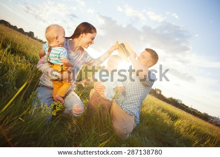 happy young family spending time in the park in sunny day (intentional sun glare, lens focus on father) - stock photo