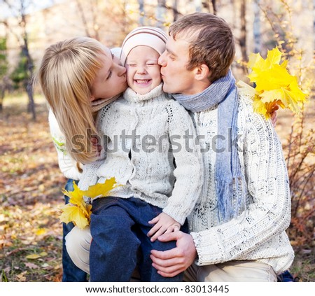 happy young family spending time outdoor in the autumn park