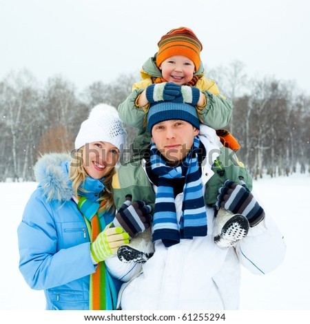 happy young family spending time outdoor in winter (focus on the father) - stock photo