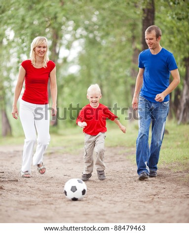 happy young family spending time outdoor on a summer day and playing ball(focus on the child)
