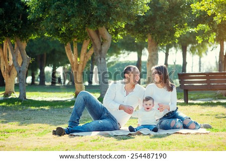 happy young family spending time outdoor on a summer day have fun at beautiful park in nature while sitting on the green grass - stock photo