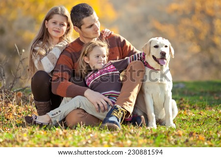 Happy young family spending time outdoor  with their dog - stock photo