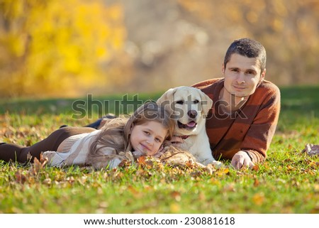 Happy young family spending time outdoor  with their dog