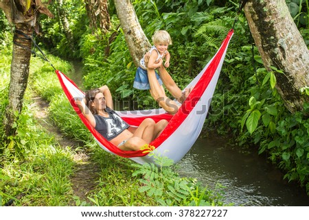 Happy young family spending time together in a hammock in green nature.