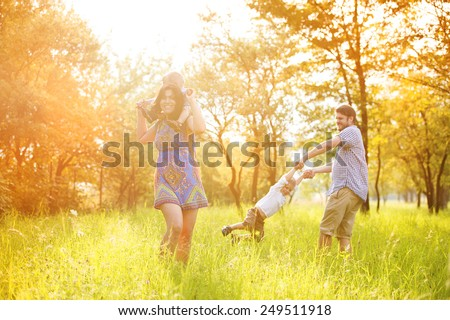 Happy young family spending time together outside in green nature. - stock photo