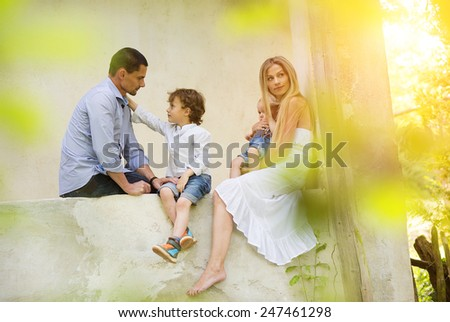 Happy young family spending time together sitting outside on a porch of old house. - stock photo