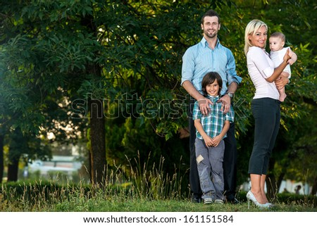 Happy young family standing outside in the park - stock photo