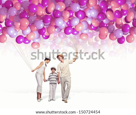 Happy young family walking holding bunch of colorful balloons