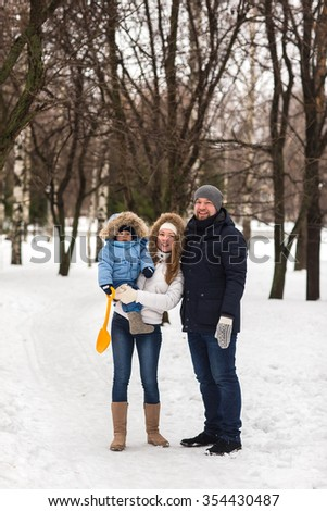 Happy young family walking in a winter park. A family of three playing in the winter snow.