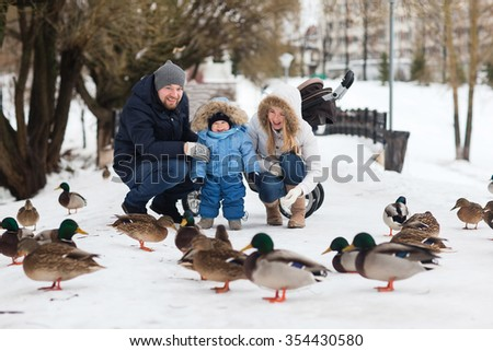 Happy young family walking in a winter park. A family of three playing in the winter snow. - stock photo