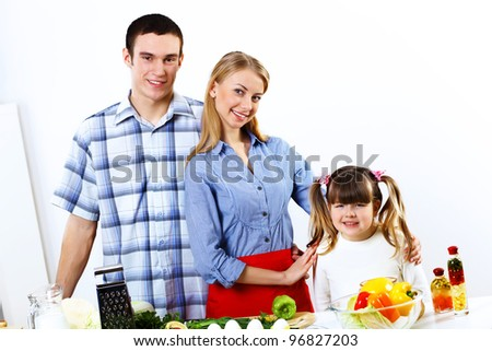 Happy young family with a daughter cooking together at home