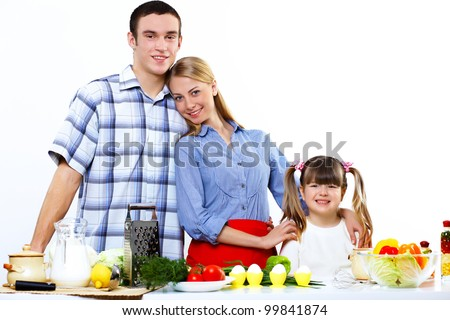Happy young family with a daughter cooking together at home - stock photo