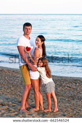 Happy young family with a heart in hands on the beach at sunset time. Summer holidays, travel, vacation concept.