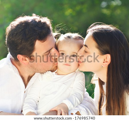 Happy young family with baby girl outdoors - stock photo