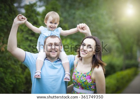 Happy young family with baby girl spending time outdoor in summer day - stock photo