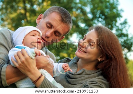 happy young family with baby in the park - stock photo