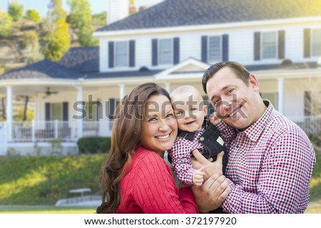 Happy Young Family With Baby Outdoors In Front of Beautiful Custom Home. - stock photo