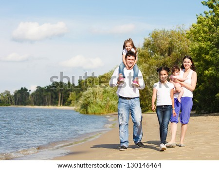 Happy young family with children outdoor in summer day - stock photo