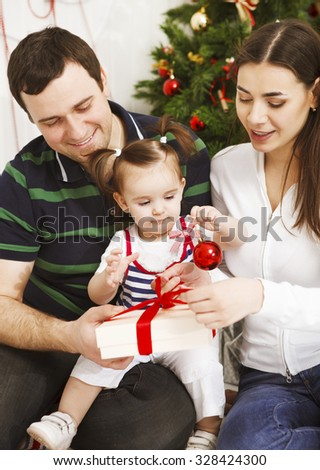 Happy young family with Christmas baby near the Christmas tree - stock photo