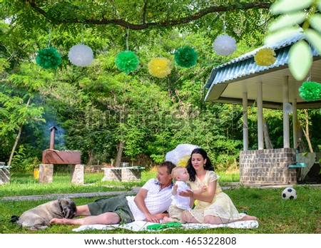 Happy young family with father, baby, mother and dog sitting outside on blanket in park with gazebo and party decorations in background