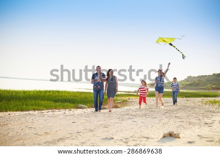 Happy young family with flying a kite on the beach. Summer vacation - stock photo
