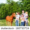 Happy young family with four children and baby horse in the spring forest - stock photo