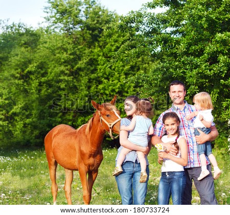 Happy young family with four children and baby horse in the spring forest