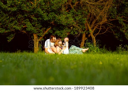 Happy young family with kid resting outdoors in green field - stock photo