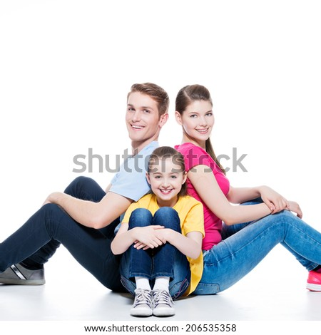 Happy young family with kid sitting on the floor at studio - isolated on white. - stock photo