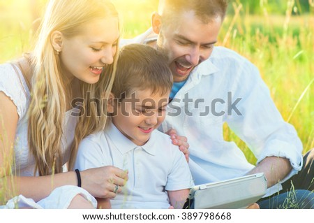 Happy Young Family with kid using Tablet PC in summer park. Dad, Mom and little boy with computer resting outdoors together. Summer holidays - stock photo