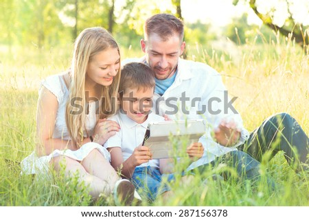Happy Young Family with kid using Tablet PC in summer park. Dad, Mom and little boy with ipad computer resting outdoors together. Summer holidays - stock photo