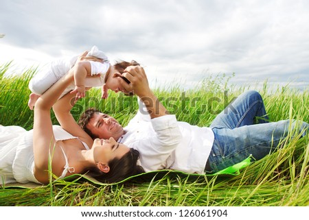Happy young family with little baby girl outdoors - stock photo