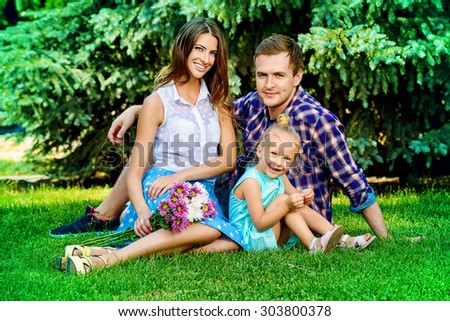 Happy young family with little daughter resting together at the park. Summer day.