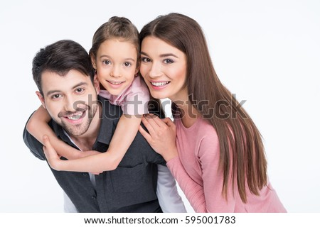 Happy young family with one child smiling at camera on white