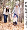 happy young family with their daughter spending time outdoor in the autumn park (focus on the man and child) - stock photo