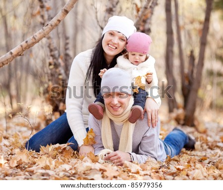 happy young family with their daughter spending time outdoor in the autumn park (focus on the  man)