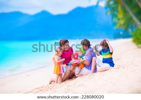 Happy young family with three children celebrating birthday party at a tropical beach. Parents with baby, teenager boy and cute little girl eating cake on summer vacation. - stock photo