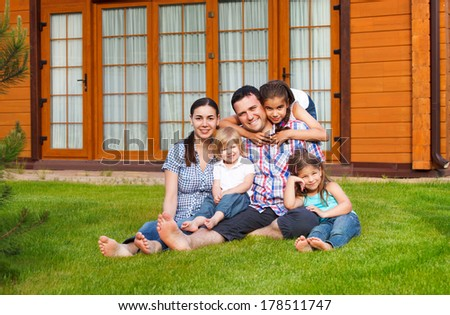 Happy young family with three children near the house