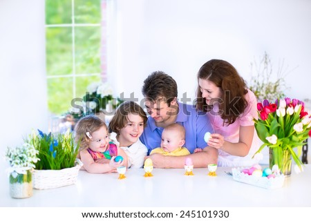 Happy young family with three children - teenager boy, cute little toddler girl with bunny ears and newborn baby - enjoying Easter breakfast in a white sunny dining room with a big garden view window  - stock photo