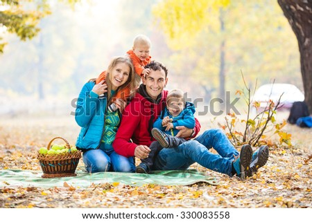 Happy young family with two boys in autumn forest - stock photo