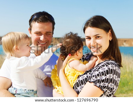 Happy young family with two children near the lake outdoors - stock photo
