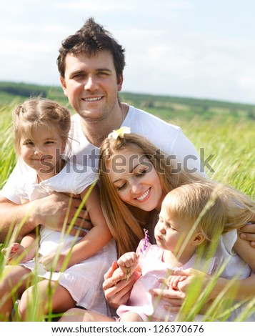 Happy young family with two children outdoors in summer day