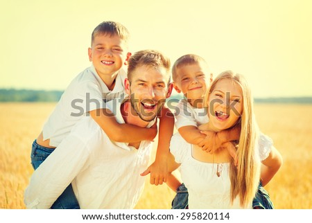 Happy Young Family with two children walking on wheat summer field. Healthy mother, father and little sons enjoying nature together, outdoors. Healthy Smiling Dad, Mom and kids together. Harvest - stock photo