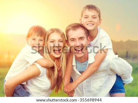 Happy Young Family with two children walking on wheat summer field. Healthy mother, father and little sons enjoying nature together, outdoors. Healthy Smiling Dad, Mom and kids together - stock photo