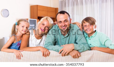 Happy young family with two kids on couch indoors