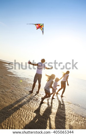 Happy young family with two kids with flying a kite on the beach - stock photo