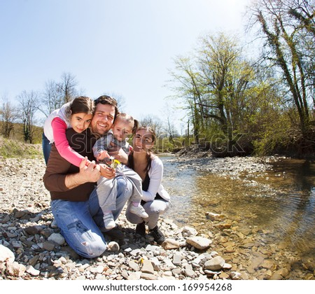 Happy young family with two little daughters near the mountain river outdoors - stock photo