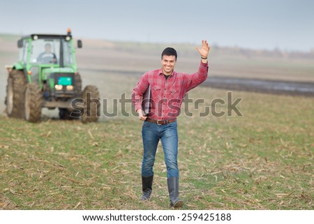 Happy young farmer waving with hand on farmland with tractor in background - stock photo